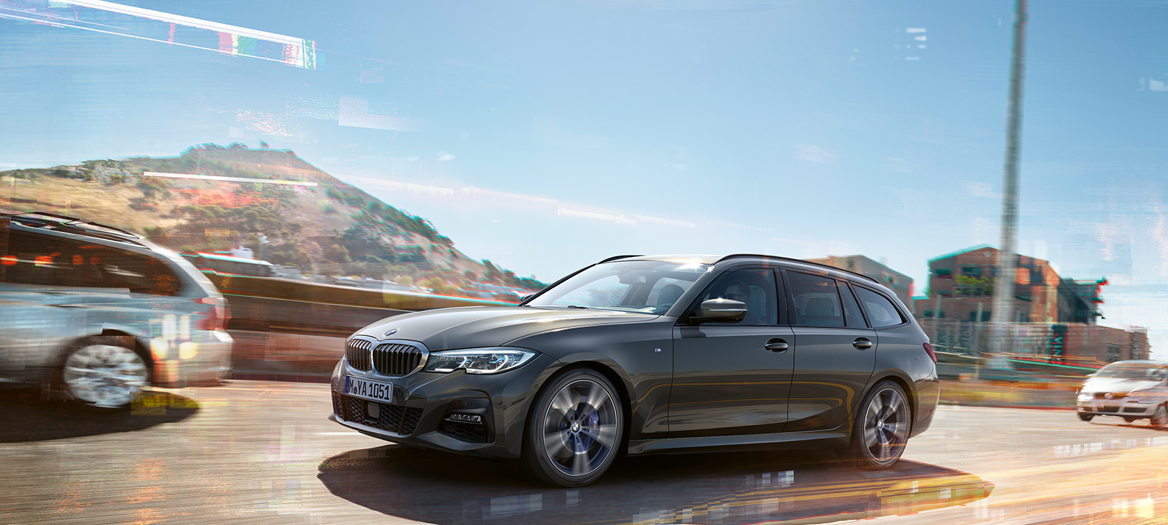 BMW Serie 3 Touring, ripresa laterale in movimento con case e montagne sullo sfondo